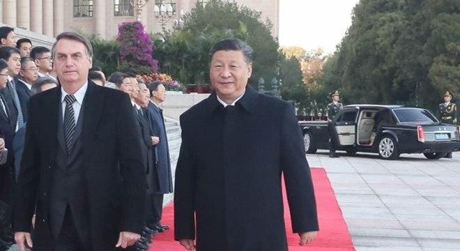 Xi Jinping e Bolsonaro em cerimonia oficial em Pequim; ao fundo, a luxuosa limusine que trouxe o brasileiro