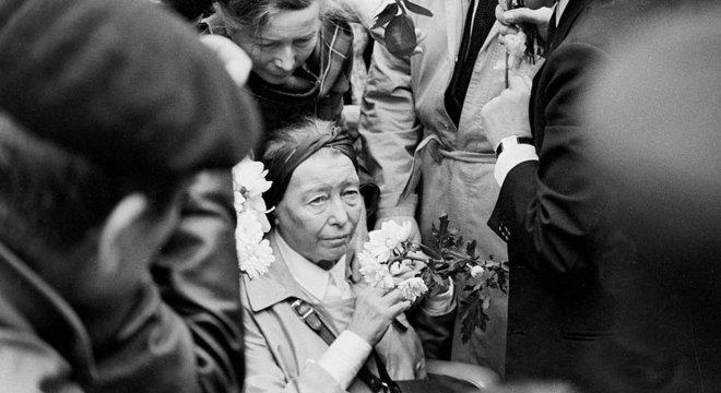 Beauvoir segura flores no funeral de Sartre, amparada por outras pessoas