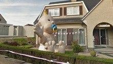 Tem um bebê inflável gigantesco em frente a uma casa na Bélgica