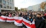 Uma multidão de milhares pessoas marchou por uma rua importante acenando com bandeiras vermelhas e brancas e cartazes de protesto