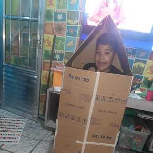 Bernardo, de 8 anos, brinca com papelão