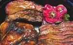"""De acordo com Beto, há dois itens da lista que são os queridinhos dos amantes de churrasco defumado. O primeiro se chama """"bandejão texano"""", que vem com quatro carnes diferentes: brisket, costela angus, pulled pork e sobrecoxa de frango desossada acompanhadas de macncheese com farofa de bacon e farofa crocante. Serve até 4 pessoas"""