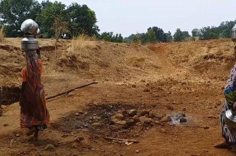 Bhuni Shelukar carrega recipiente com água, sobre a cabeça, em área onde temperaturas beiram os 50 graus