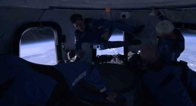 Tripulantes da New Shepard interagem durante experiência de viajar ao espaço