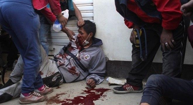 Homem ferido é atendido na rua em Senkata, na Bolívia