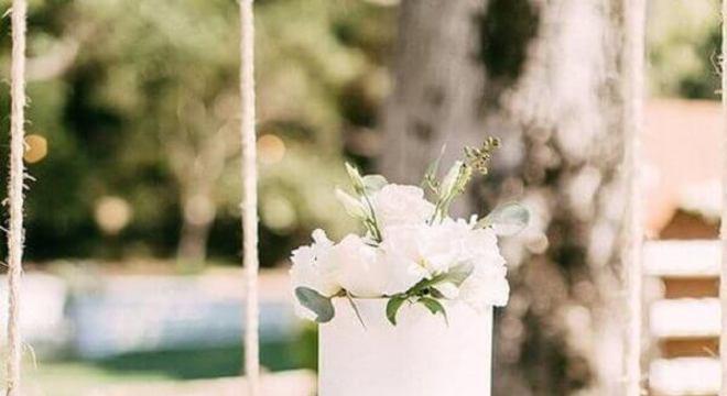 bolo de casamento branco decorado com folhas e flores