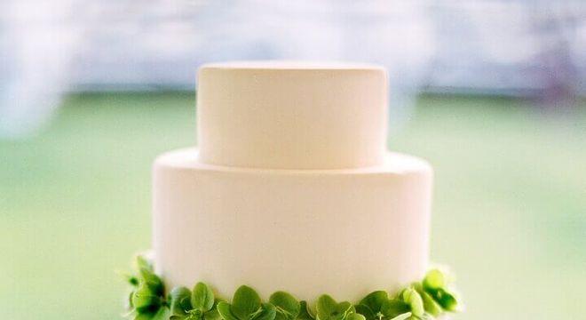 bolo de casamento branco decorado com folhas verdes