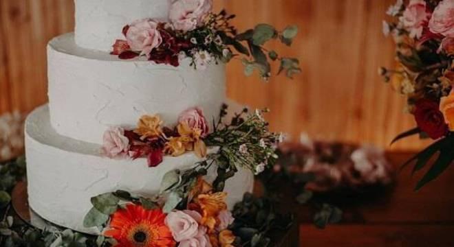 Bolo de festa decorado com fundo branco e flores de gérbera encanta a decoração da mesa