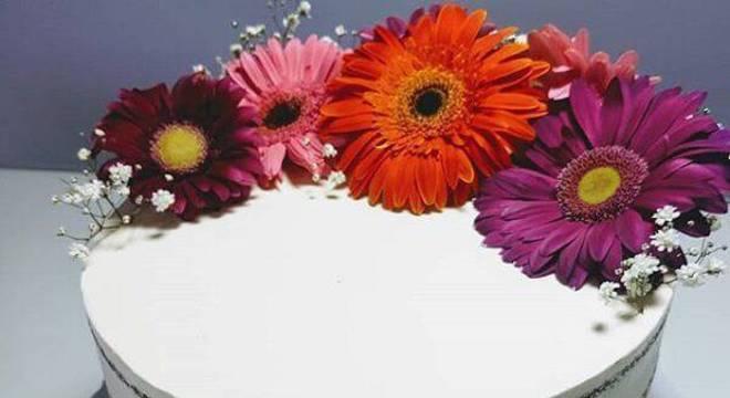 Bolo simples com topo formado por flores de gérbera