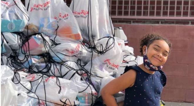Menina distribui bolsas com suprimentos para pessoas carentes