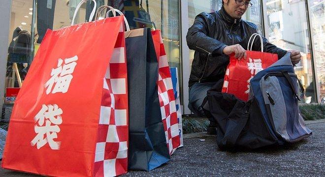A palavra fukubukuro, em japonês, aparece escrito nessas bolsas vermelhas de papel