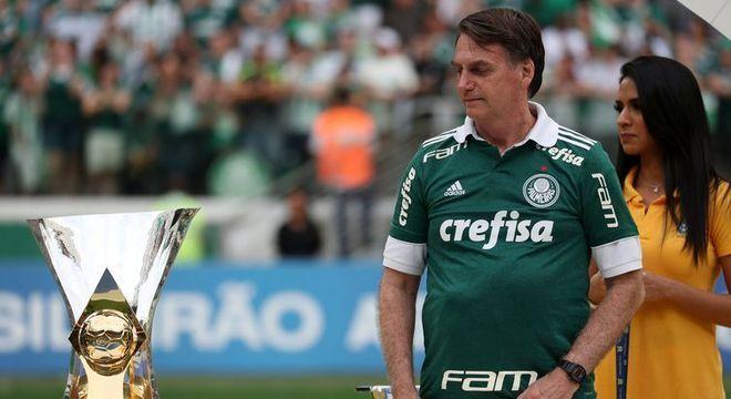 Bolsonaro, com a camisa do Palmeiras, admirando a taça do decacampeonato