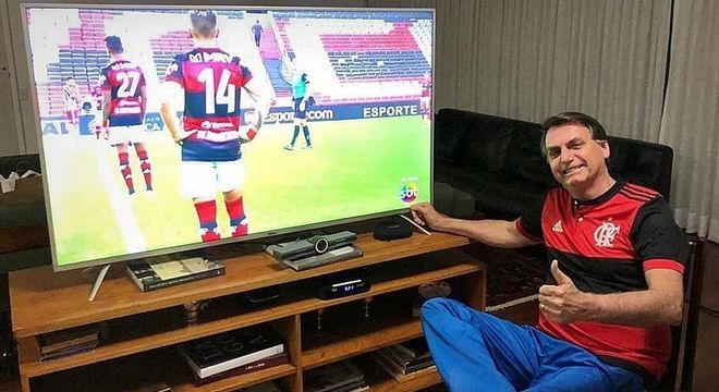 Bolsonaro assistindo à final do Carioca. MP conseguiu tirar o jogo da Globo
