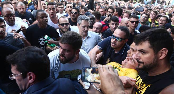 Bolsonaro (de camiseta amarela) é carregado por apoiadores logo após ataque em MG