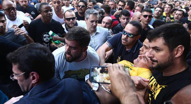 O candidato Jair Bolsonaro é carregado durante evento em Juiz de Fora