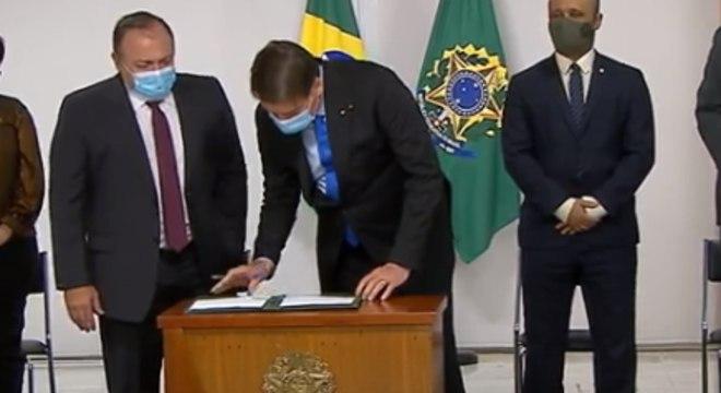 O presidente Jair Bolsonaro assina MP durante solenidade no Palácio do Planalto