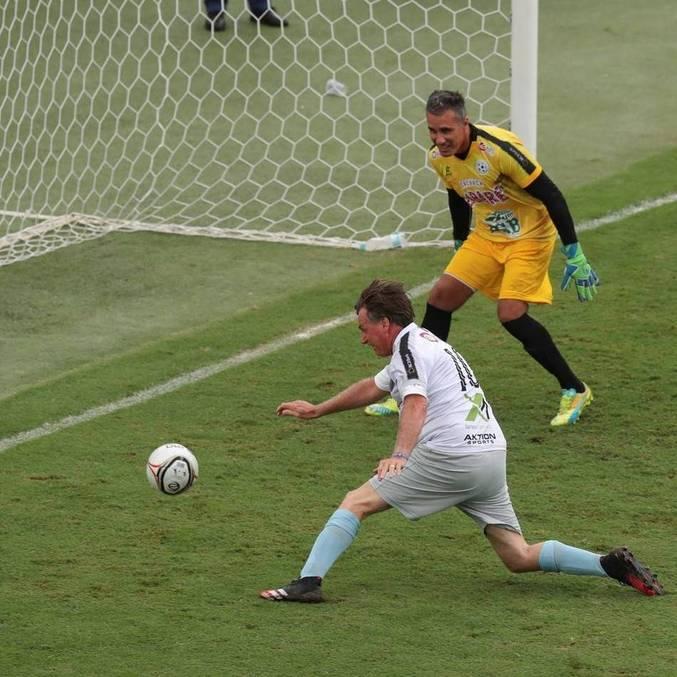 Presidente Jair Bolsonaro chuta com o pé esquerdo para marcar um gol em jogo beneficente
