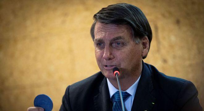 O presidente Jair Bolsonaro segura moeda de nióbio, em evento em Brasília