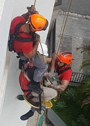 bombeiros resgatam funcionário suspenso durante serviço de manutenção em prédio