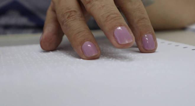 Mulher faz leitura de material em braile na Fundação Dorina Nowill