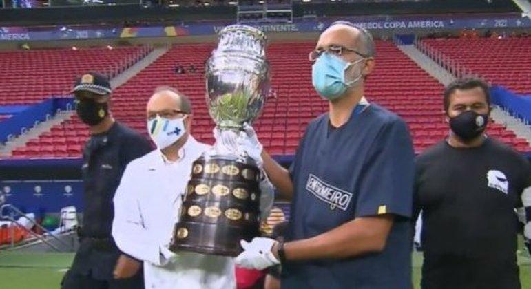 A imagem que melhor representa a Copa América. Médico e enfermeiro apresentam o troféu