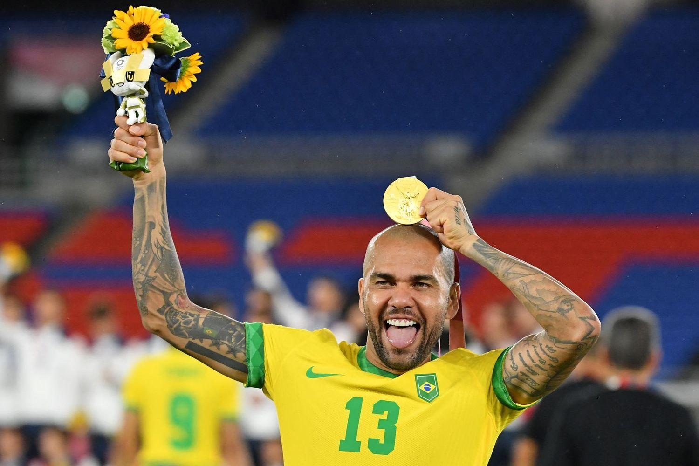 Daniel Alves com a medalha. Sem o agasalho da Peak. Mostrando a camiseta com o emblema da Nike