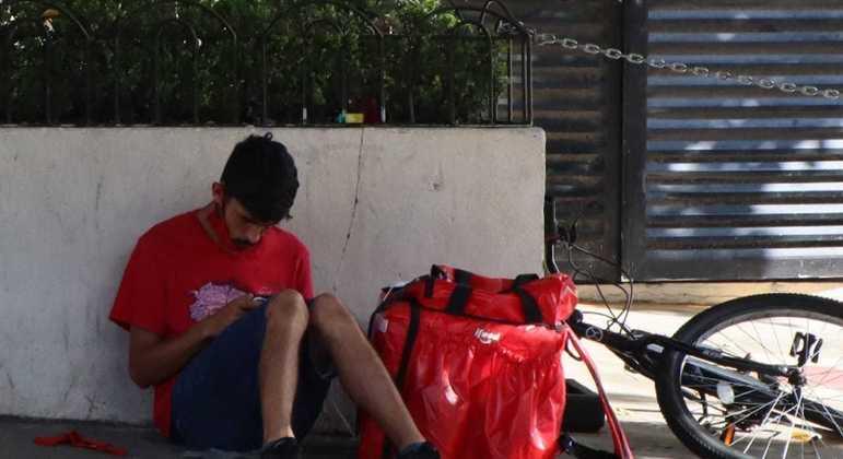 Entregador na calçada do Shopping Metrô Santa Cruz, descansando enquanto espera app solicitar entrega