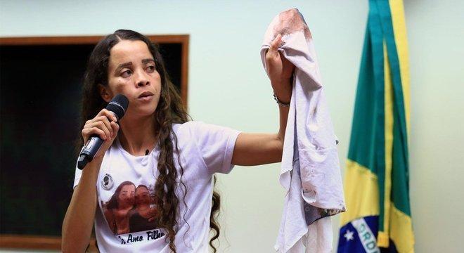 Bruna Silva levou a camisa do uniforme escolar do filho, manchada de sangue, para protestos, entrevistas, encontros com autoridades. Aqui, ela aparece em depoimento à Câmara dos Deputados, em julho de 2018