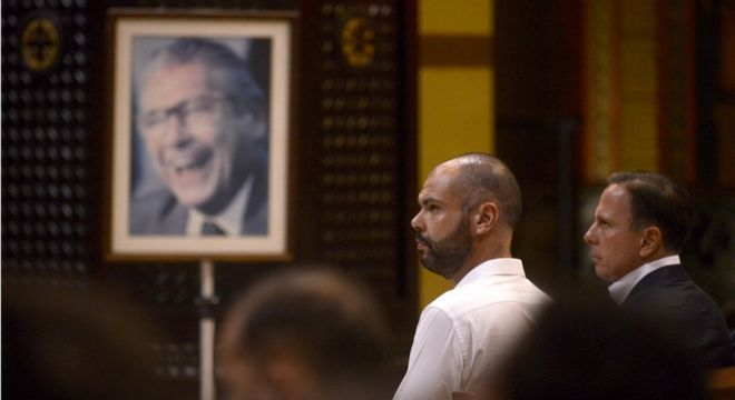 Bruno Covas ao lado de João Doria e foto de Mário Covas ao fundo; futuro prefeito de SP faz reverências frequentes ao avô