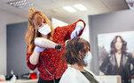 Cabelereira de máscara secando cabelo de cliente.