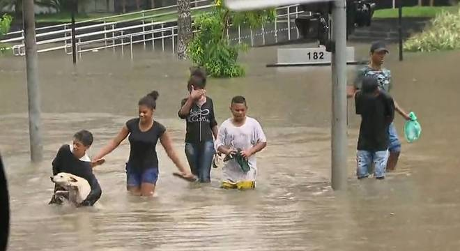 Garoto tenta levar o cachorro para longe da enchente