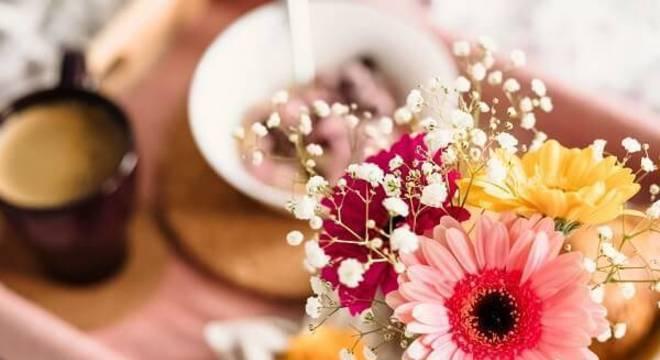 Café na cama acompanhado de um mini vaso com flores de gérbera