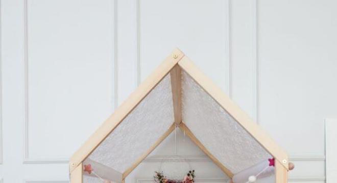 Cama casinha de madeira com manta rosa na decoração