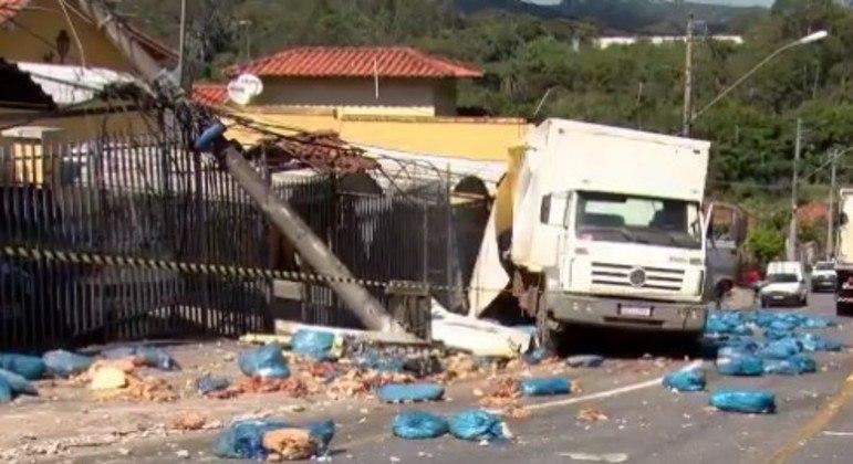 Caminhão arrancou poste, derrubou muro de casa e carga ficou espalhada na rua