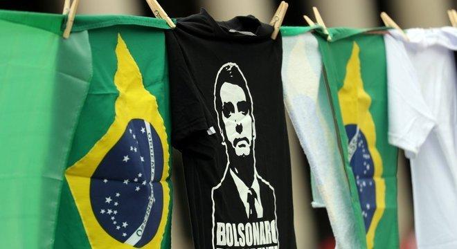 Camiseta de Bolsonaro pendurada em varal, ao lado de bandeiras do Brasil
