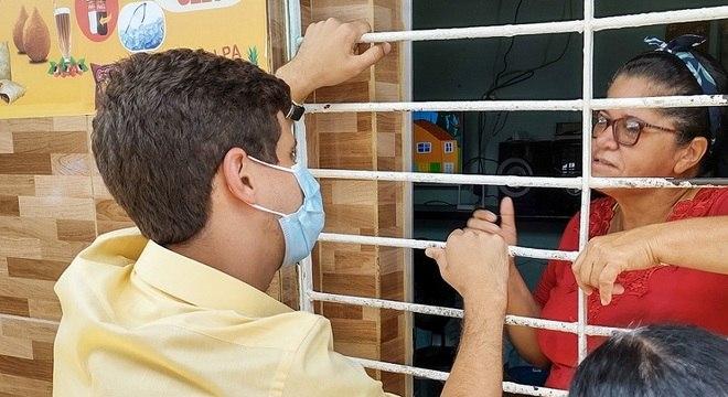 De máscara, pré-candidato à Prefeitura de Recife busca eleitores em casa