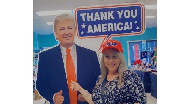 Candy em uma foto com a imagem de Donald Trump em papelão