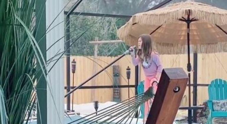 Menina foi flagrada por seu pai enquanto cantava ao limpar a piscina