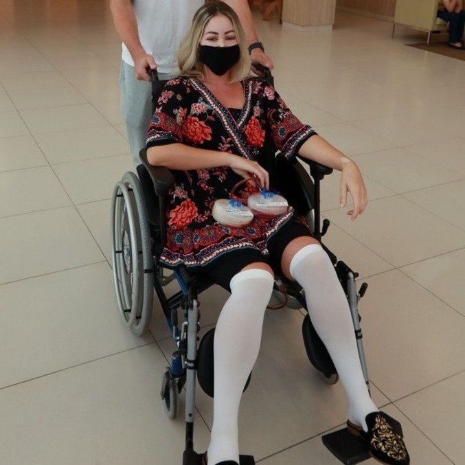 Modelo deixou o hospital  segurando os drenos deixados após a cirurgia estética