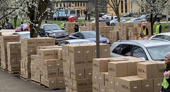Muitos bancos de alimentos estão recorrendo à distribuição de comida em sistema de 'drive-thru', nos quais voluntários colocam uma caixa com mantimentos diretamente no porta-malas do carro
