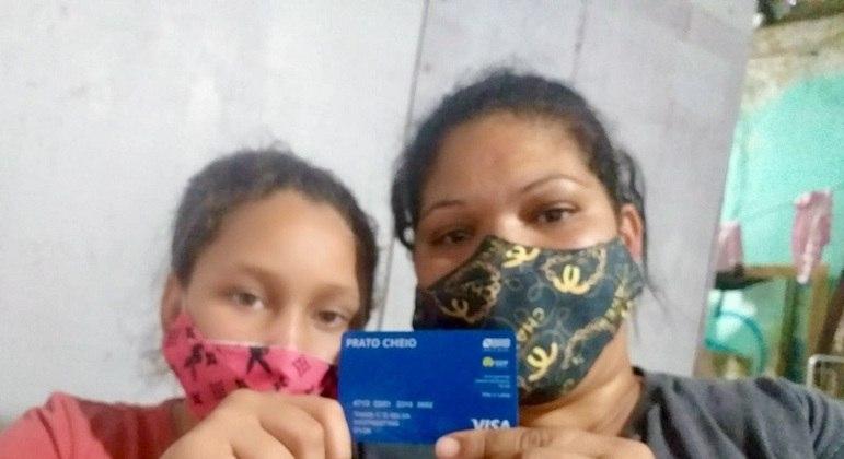 Thaís Cristina Dias da Silva, beneficiária do Prato Cheio, e uma de suas filhas