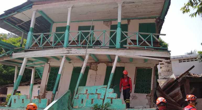 Militares dos bombeiros inspecionam casa destruída por terremoto no Haiti.