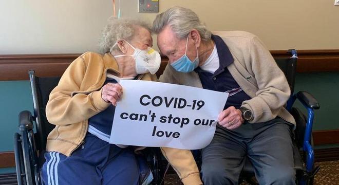 """Casal com a placa """"Covid-19 não parou nosso amor"""""""
