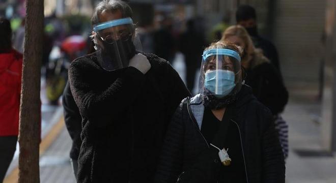 Casal se protege contra o coronavírus na ruas de Santiago, capital do Chile