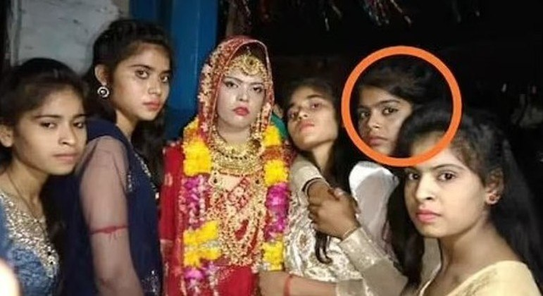 Imagem tirada um dia antes do casamento: a noiva ao centro e irmã com um círculo vermelho