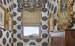 O papel de parede estampado em ambiente pequeno conflita com os quadros e a moldura cheia de detalhes