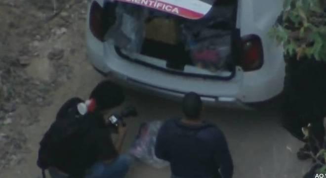 Polícia científica fotograva patins retirados do local onde o corpo foi encontrado