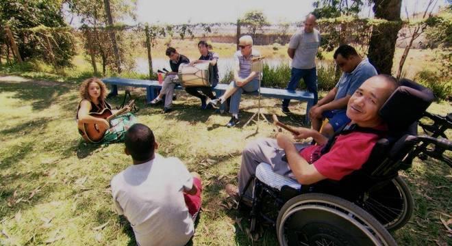Várias pessoas reunidas em uma roda de musicoterapia em um belo gramado aberto à sombra de algumas árvores.