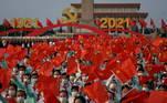 Dezenas de milhares de espectadores cuidadosamente escolhidos, reunidos na imensa Praça da Paz Celestial (Tiananmen), aplaudem a passagem da bandeira gigante, carregada por um helicóptero