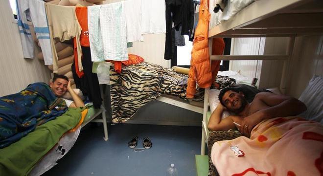 Homens descansam em centro de acolhida de imigrantes na Lampedusa, na Itália